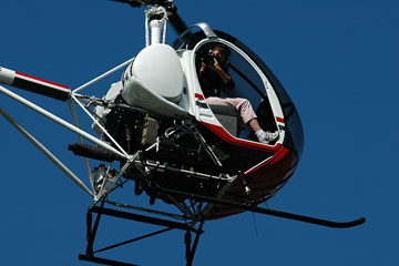 an aerial photographer taking photos from a helicopter